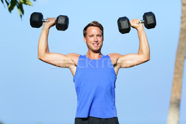 Fitness man dumbbell weights training outside Stock photo © Maridav
