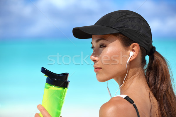 Healthy Asian girl drinking water listening music Stock photo © Maridav