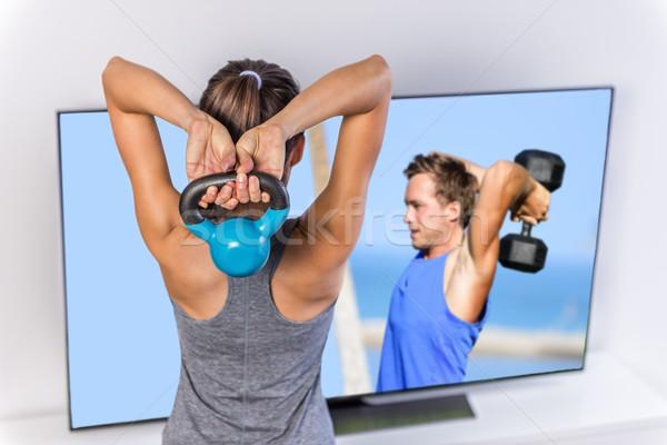 Fitness at home - woman following TV workout video Stock photo © Maridav