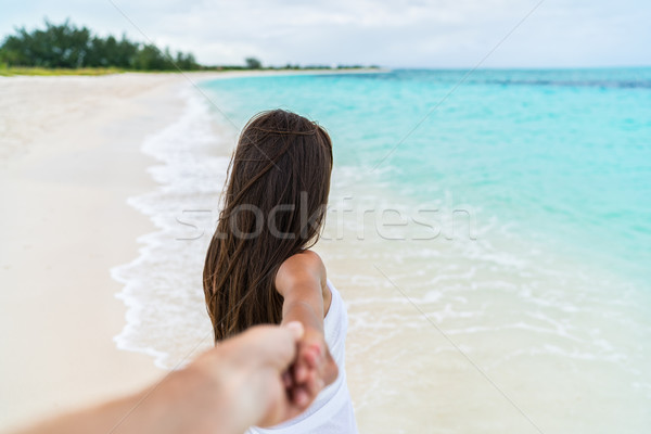 POV of couple walking - boyfriend following girlfriend holding hand on beach Stock photo © Maridav