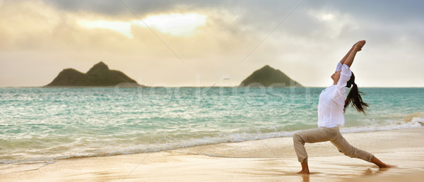 Yoga woman meditating in warrior I pose at beach Stock photo © Maridav