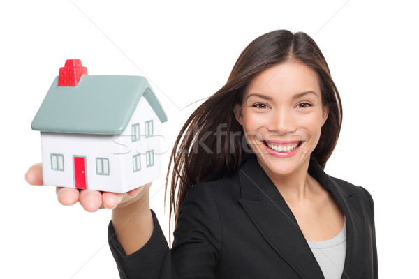 Real estate agent selling home holding mini house Stock photo © Maridav