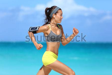 Asian fitness woman with sports bra and armband Stock photo © Maridav