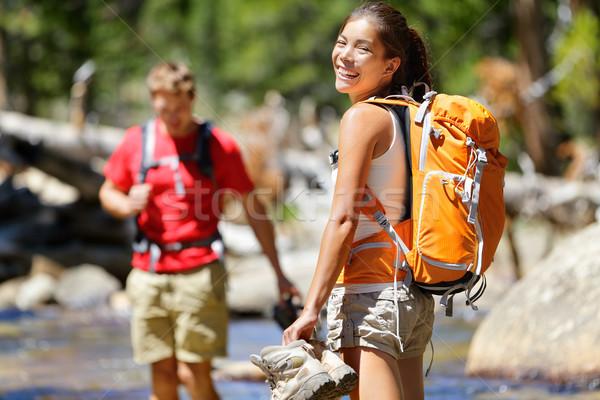 Hiking friends having fun crossing river in forest Stock photo © Maridav
