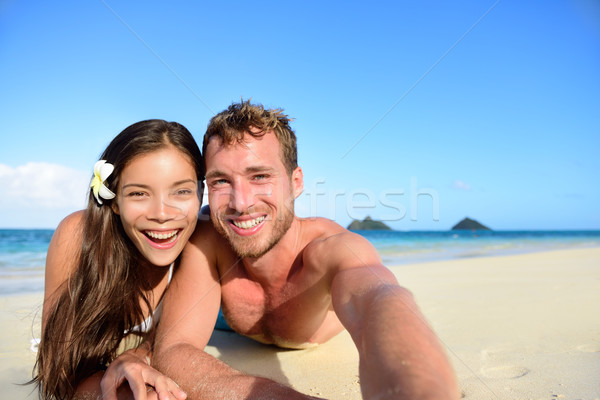 Stock photo: Couple relaxing on beach taking selfie picture