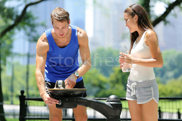 Public park water fountain couple runners drinking Stock photo © Maridav