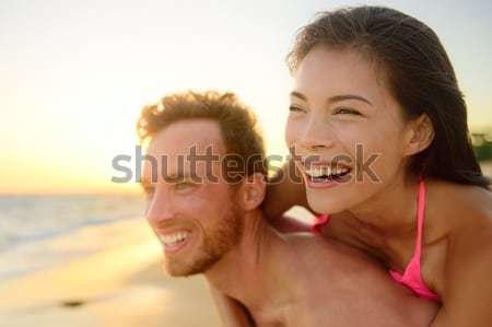Beach couple laughing in love having fun romance Stock photo © Maridav