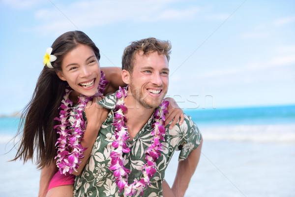 Happy beach couple having fun piggybacking Stock photo © Maridav