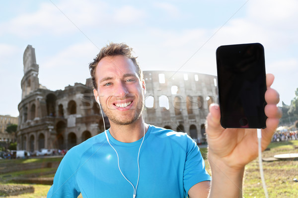 Smiling Jogger Showing Smartphone Against Colosseum Stock photo © Maridav