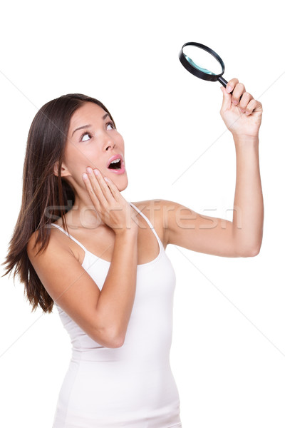 Surprised woman searching with magnifying glass Stock photo © Maridav