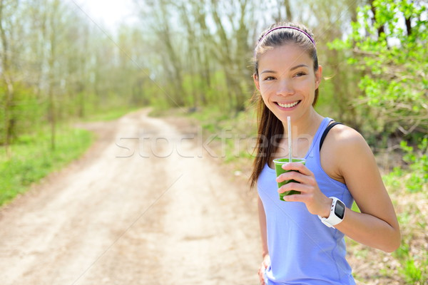 Woman drinking green smoothie wearing smartwatch Stock photo © Maridav
