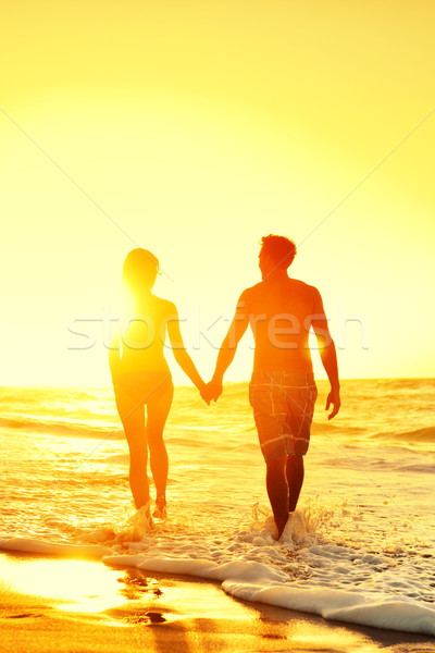 Beach couple holding hands together at sunset Stock photo © Maridav