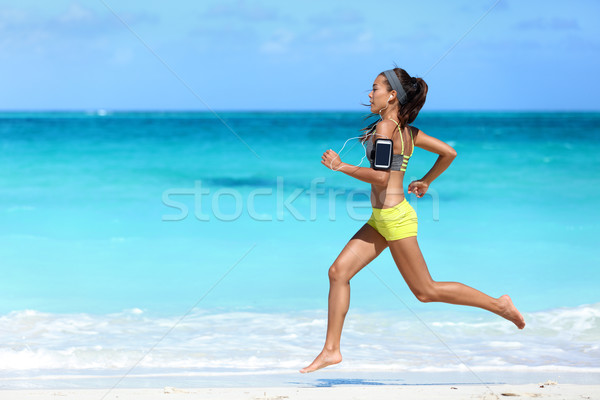 Fitness runner woman beach running listening to music with phone sport armband Stock photo © Maridav