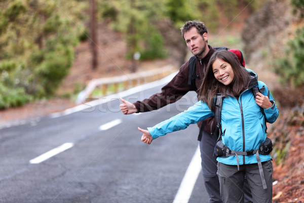 Travel hikers couple hitchhiking on road trip Stock photo © Maridav