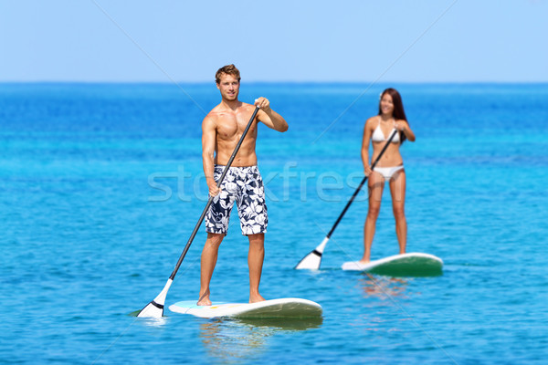 Couple Doing Stand Up Paddleboarding On Ocean Stock photo © Maridav