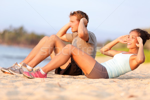 Situps on beach - young couple happy training Stock photo © Maridav