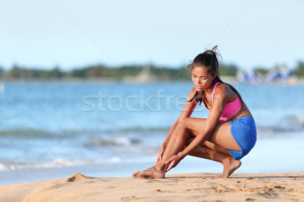 Jogger Suffering From Ankle Pain On Beach Running Stock photo © Maridav