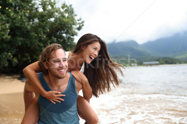 Happy young couple doing piggyback on beach travel Stock photo © Maridav