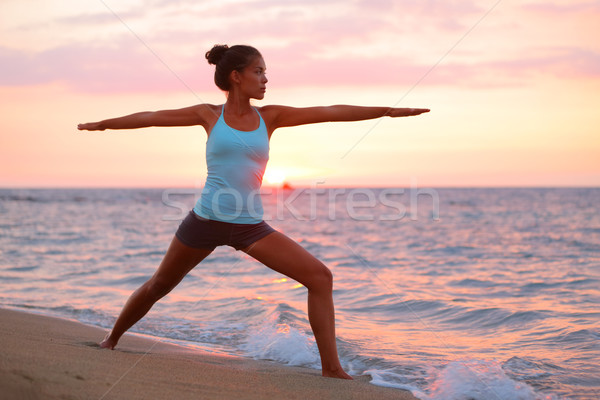 Yoga woman in meditating in warrior pose at beach Stock photo © Maridav