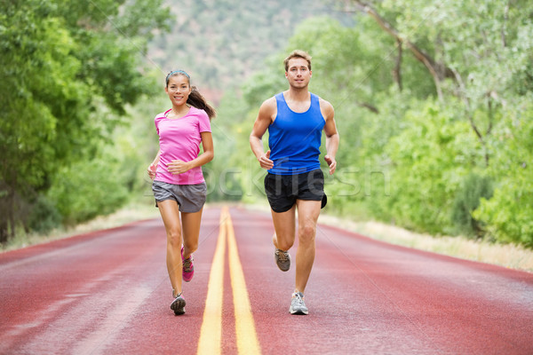 Running young couple outside jogging happy smiling Stock photo © Maridav