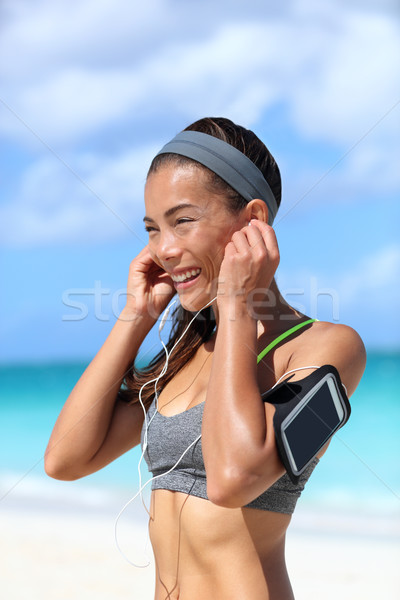 Runner girl putting earphones and running armband Stock photo © Maridav