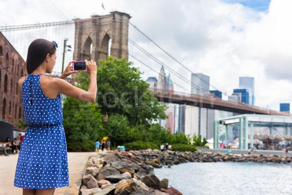 Tourist taking travel picture with phone of Brooklyn bridge, New York Stock photo © Maridav