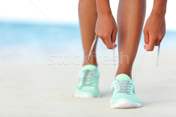 Runner woman tying laces of running shoes preparing for beach jogging Stock photo © Maridav