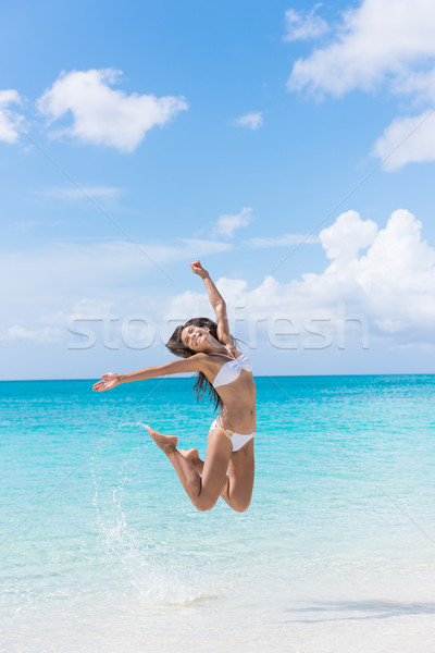 Fun bikini woman jumping on beach splashing water Stock photo © Maridav