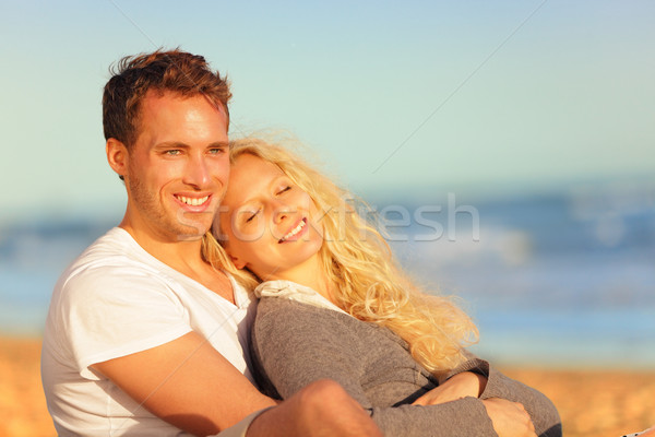 Romantic lovers relaxing at sunset beach Stock photo © Maridav
