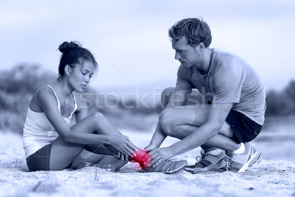 Sprained ankle - trainer helping runner in pain Stock photo © Maridav
