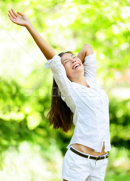Happy Young Woman Raising Arms In Park Stock photo © Maridav