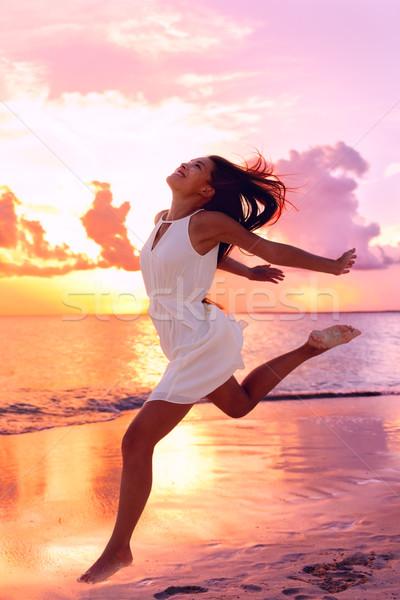 Carefree Woman Jumping At Beach During Sunset Stock photo © Maridav