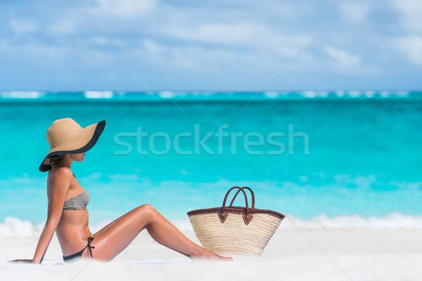 Sexy bikini woman sun tanning - beach bag and hat Stock photo © Maridav