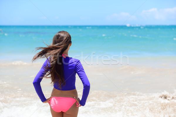 Beach girl going swimming in rashguard swim shirt Stock photo © Maridav