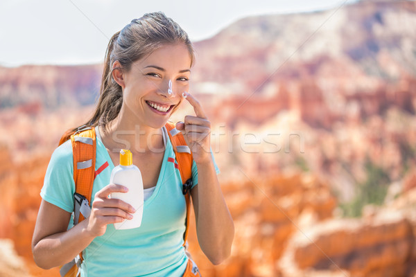 Hiker sunscreen - Woman hiking putting sunblock Stock photo © Maridav