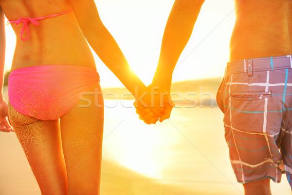 Holding hands couple in swimwear at beach Stock photo © Maridav