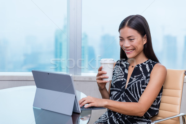 Happy young professional on laptop drinking coffee Stock photo © Maridav