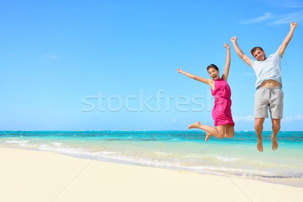 Beach vacation - happy fun tourists couple jumping Stock photo © Maridav
