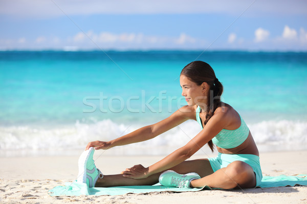 Fitness woman stretching legs on beach - Sporty Asian girl doing leg stretch  Stock photo © Maridav