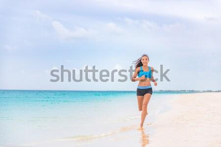 Healthy and active running woman jogging on beach Stock photo © Maridav