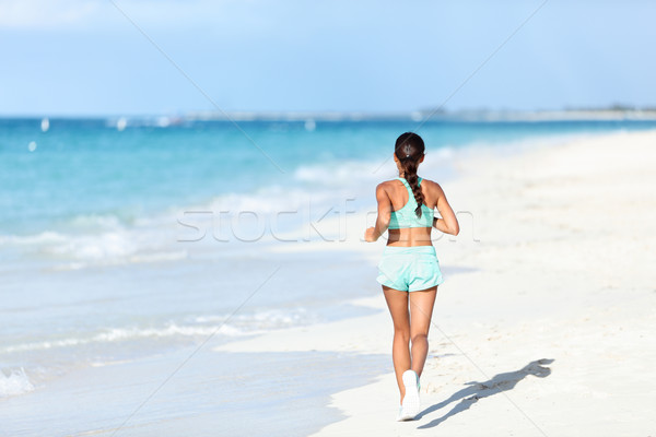Sporty runner in running outfit training cardio jogging on sunny beach Stock photo © Maridav