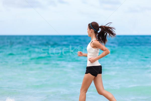 Fitness athlete training cardio running on beach Stock photo © Maridav