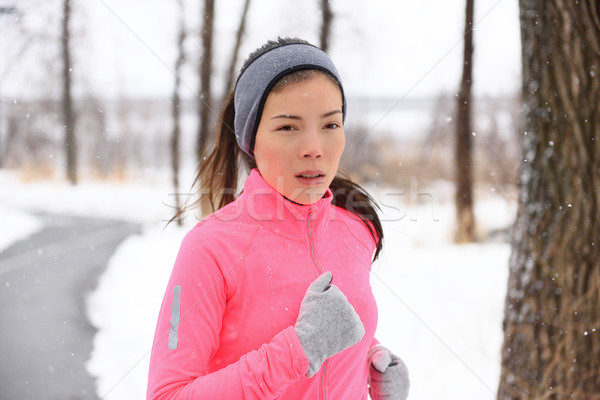 Asian woman running in winter gloves and headband Stock photo © Maridav