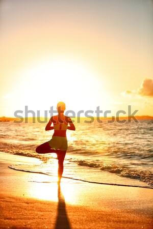 Yoga fitness woman practicing tree pose on beach at sunset Stock photo © Maridav
