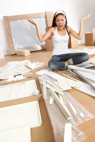 Stock photo: woman moving in - furniture assembly frustration