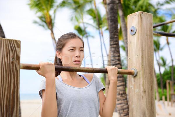 Fitness woman exercising on chin-up bar Stock photo © Maridav