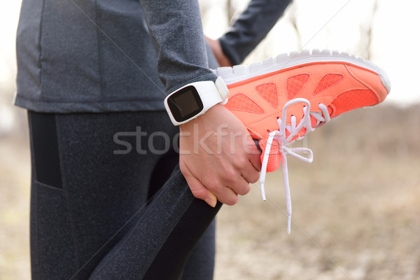 Running stretching - runner wearing smartwatch Stock photo © Maridav