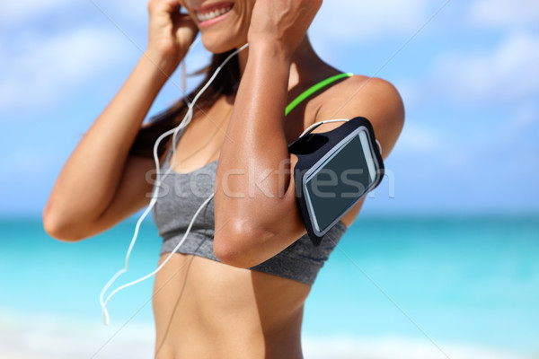 Fitness phone armband woman putting earphones Stock photo © Maridav