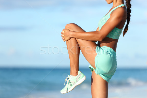 Runner stretching leg during outdoor warm-up on beach before run Stock photo © Maridav