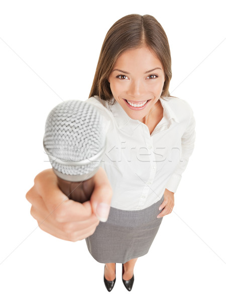 Smiling woman offering up a microphone Stock photo © Maridav